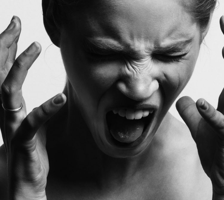 Psychologically stressed and frustrated women screaming with her hands up to her head
