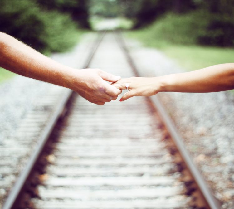 Couple's arms stretched across a railway holding hands