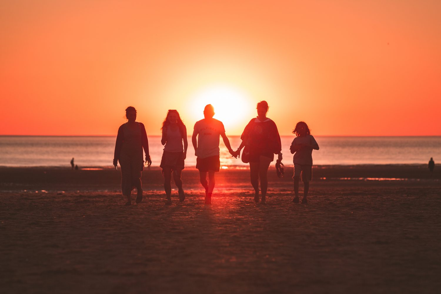 silhouette photo of five person walking on seashore during sunset
