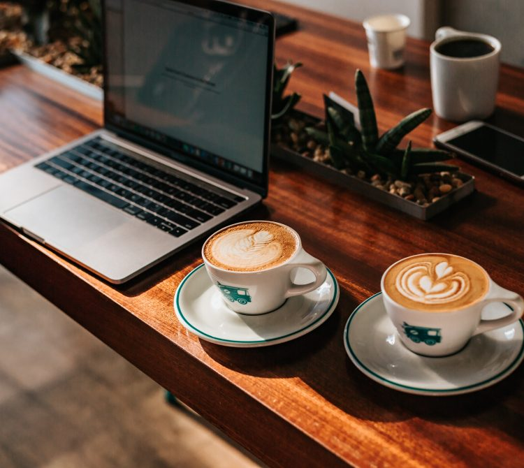 two coffees on wooden table with laptop