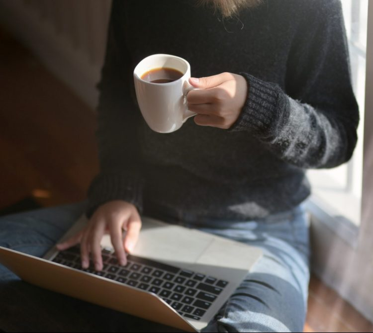 women using lap top while holding a cup of coffee