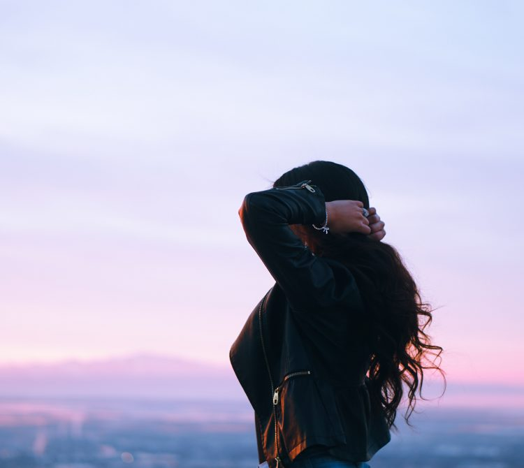 women holding her hair looking at sunset
