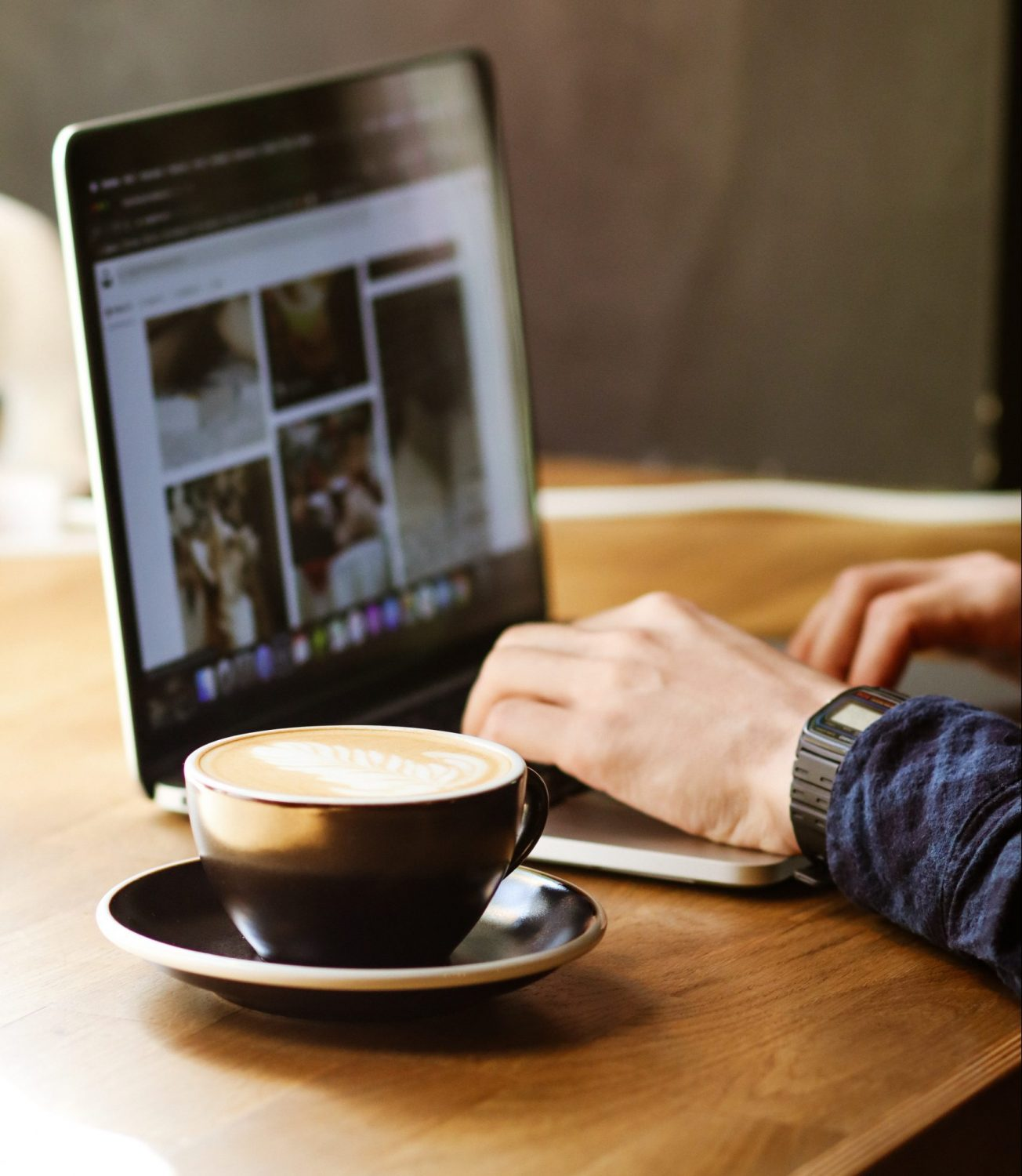 man typing at laptop with coffee