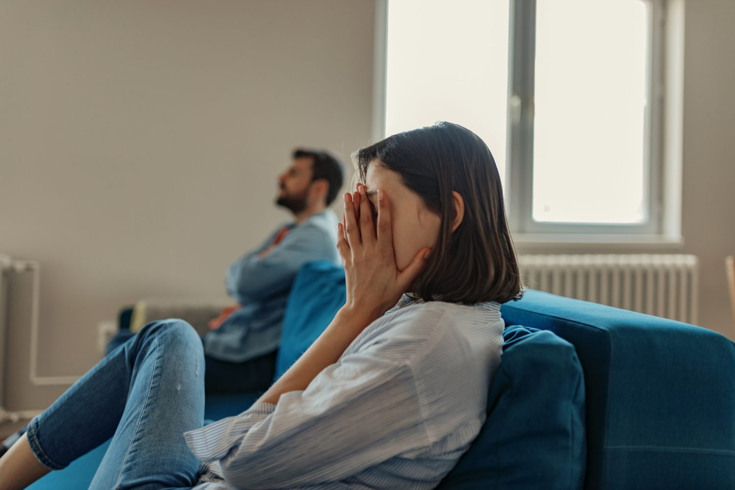Unhappy Couple After an Argument sitting on the couch in the living room