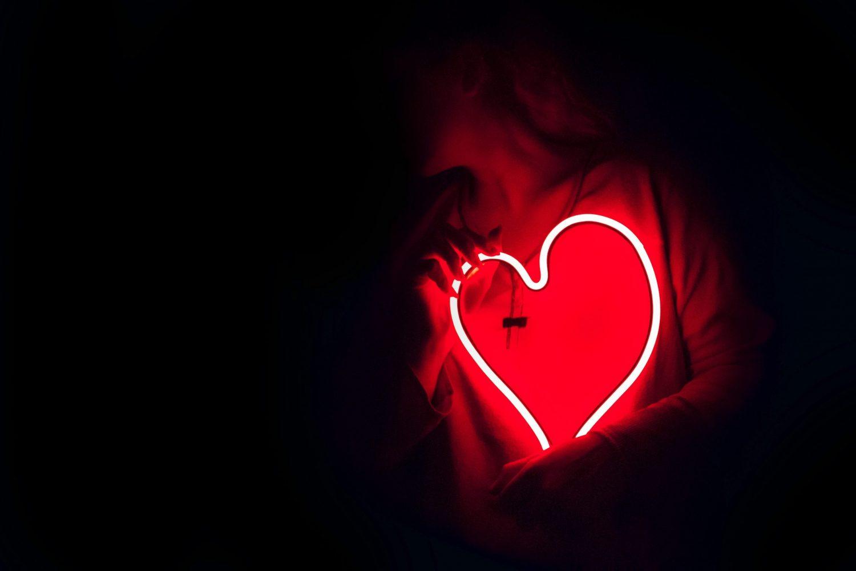 Women holding neon lighting heart on her chest