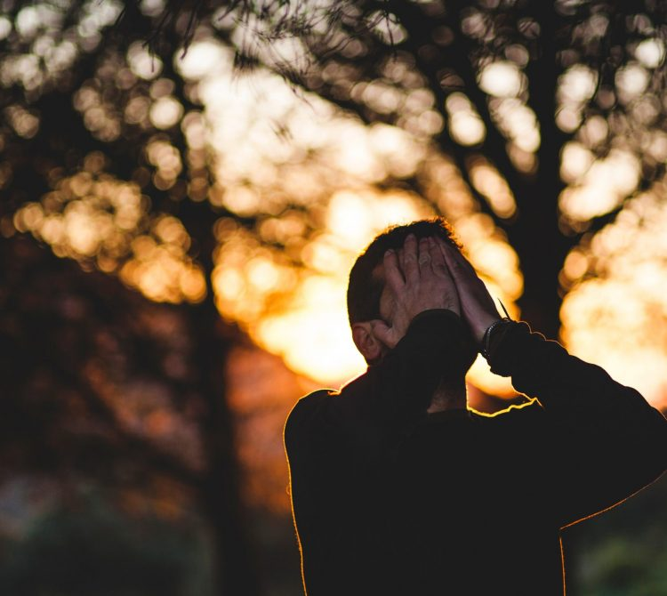 Man with hands on his face looking up as he experiences stress