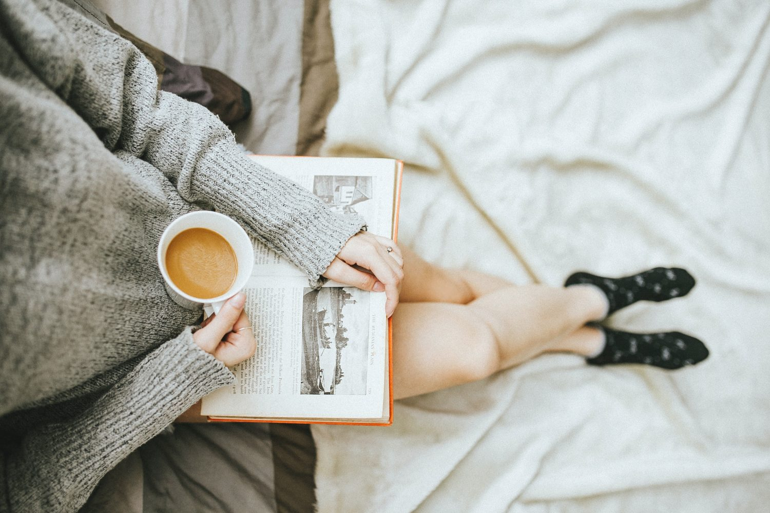 Woman relaxed, drinking a cup of tea and reading a book as a way to overcome her anxiety