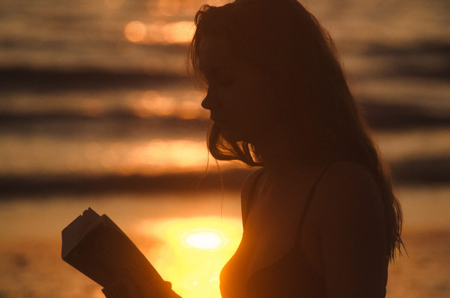 Young woman reading a book while the sun is setting
