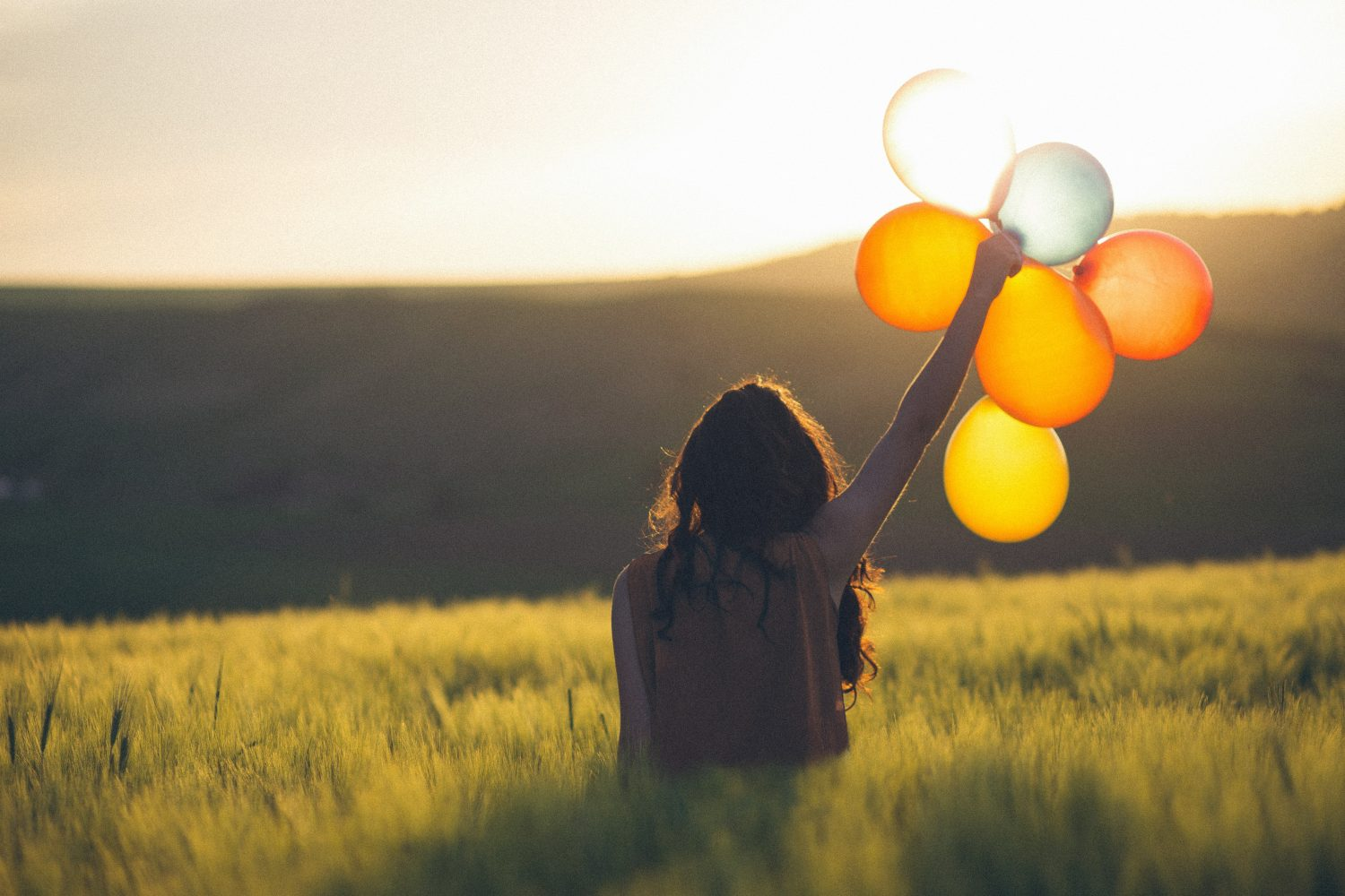 Girl holding balloons in field creating a happiness spike